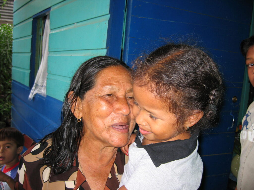 Enrique's paternal grandmother María stands in front of her Tegucigalpa home and holds Jasmín in 2003.