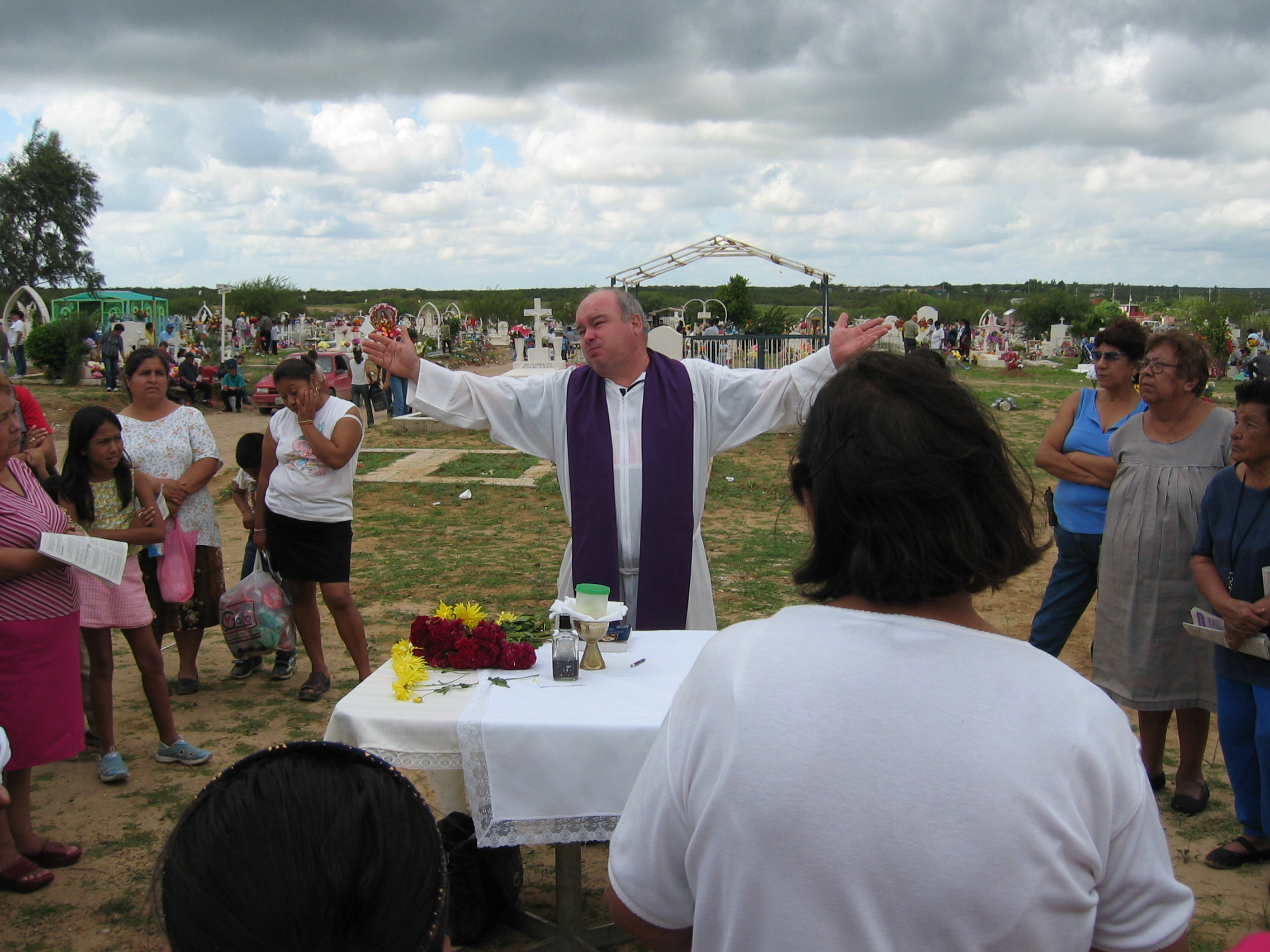 On the Day of the Dead in 2003, Father Leonardo López Guajardo says mass at the Nuevo Laredo cemetery. He also led a prayer for migrants buried in a common grave.