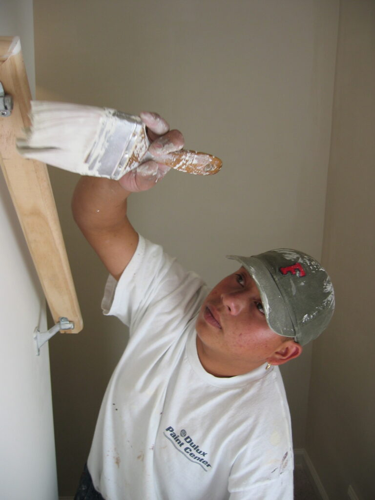Enrique paints a new home in North Carolina in 2003.[Credit: Sonia Nazario]