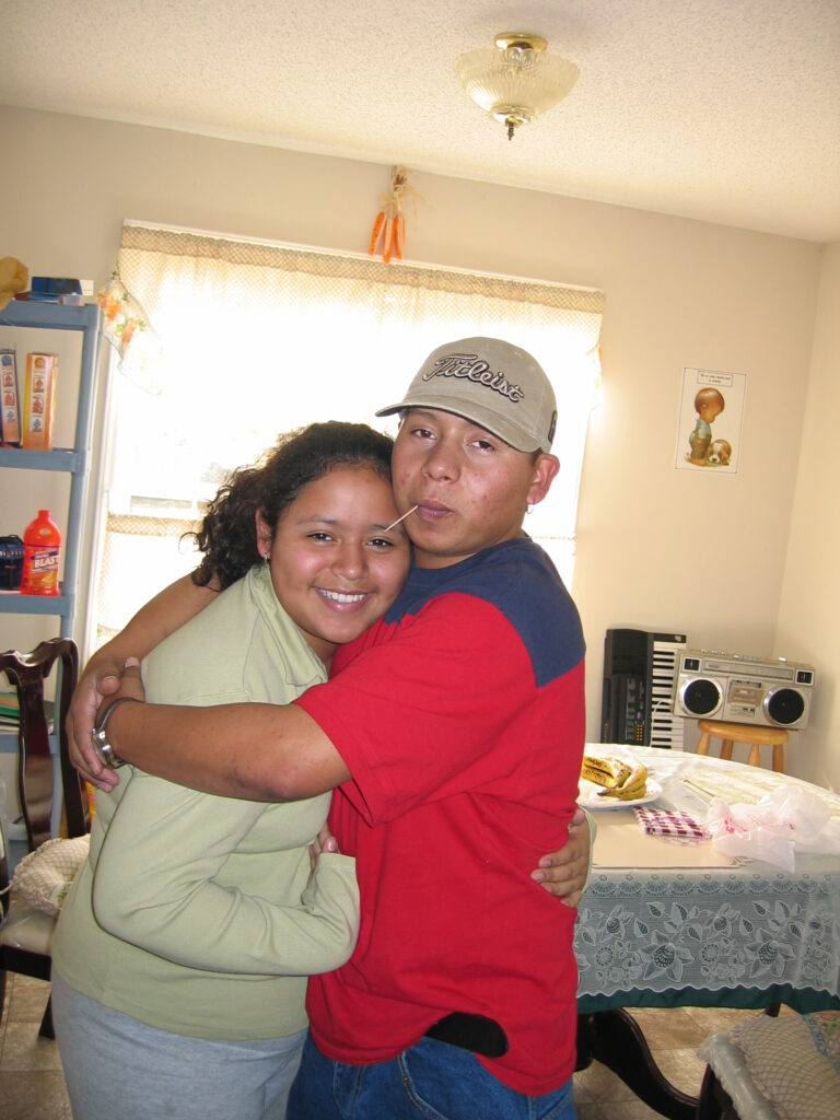 Enrique and sister Diana share a hug, 2003. [Credit: Sonia Nazario]