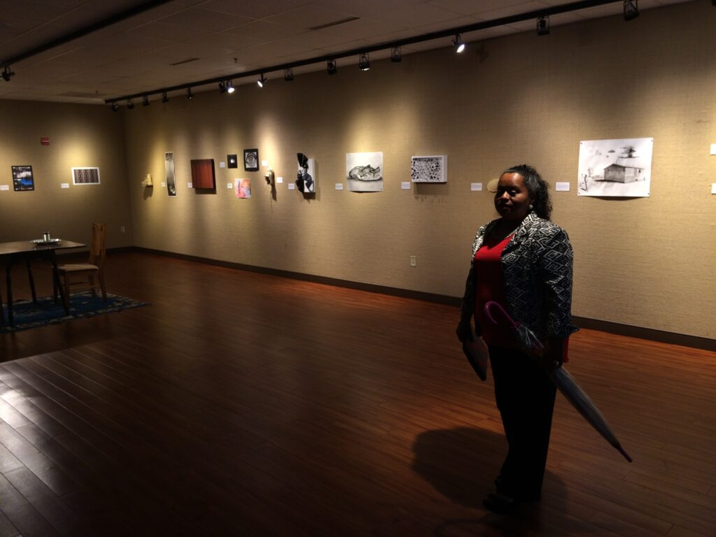 Lourdes viewing art inspired by Enrique's Journey at Sam Houston State University, November 2015. [Credit: Sonia Nazario]