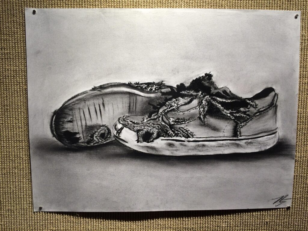 This piece was created by student Mallorie Giasson at Sam Houston State University. The tattered shoes are meant to represent the completion of Enrique's journey to reunite with his mother.